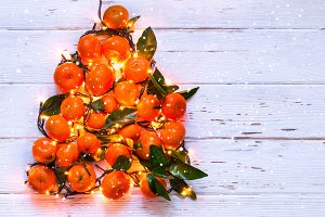 Christmas New Year tree of tangerines and burning garlands