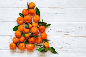 Christmas New Year tree of tangerines on white wooden background