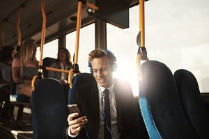 Young businessman smiling and listening to music during his commute