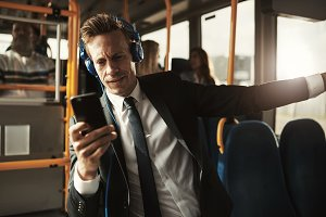Young businessman listening to music while riding on a bus
