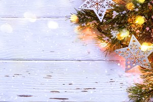 Christmas snowy background. Fir branches with burning garland, banner long format