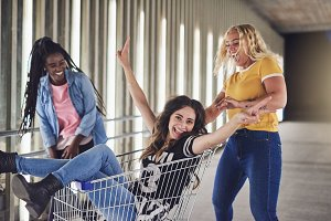 Young girlfriends playing with a shopping cart at night