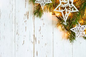 Christmas snowy background. Fir branches with burning garland