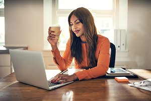 Smiling young entrepreneur working in her home office drinking coffee