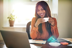 Young woman drinking coffee while working in her home office