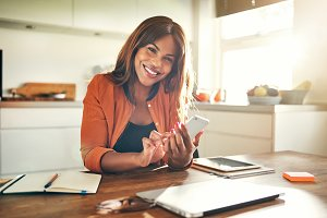 Smiling entrepreneur reading texts while working at her kitchen table