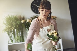 Young female florist making a bouquet in her flower shop