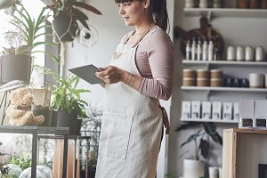 Female florist standing in her flower shop using a tablet
