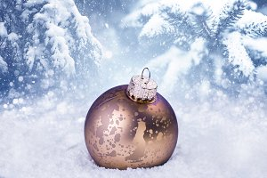 Gold Christmas ball in the snow