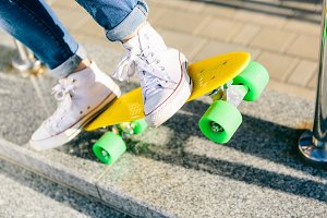 Pretty sporty woman with skateboard.