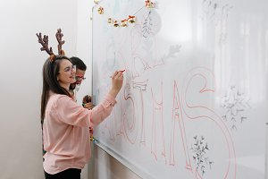 Coworkers writing merry Christmas on the whiteboard