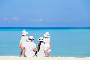 Back view of a happy family in white on the beach