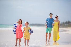 Young family on the beach. Little kids with towels