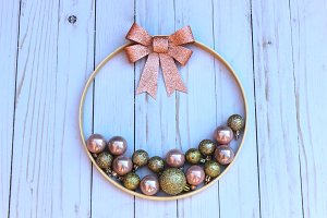 Pink & gold ornaments in wood hoop