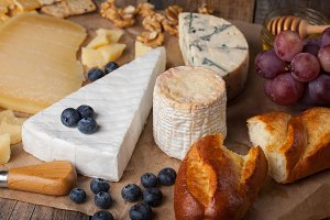 Tasting cheese dish. Food for wine and romantic, cheese delicatessen on a wooden rustic table
