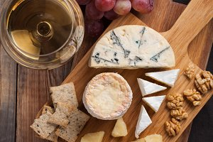 Tasting cheese dish on a wooden plate. Food for wine and romantic, cheese delicatessen on a wooden rustic table. Top view