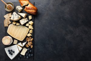 Tasting cheese dish on a dark stone plate. Food for wine and romantic date, cheese delicatessen on a black concrete background. Top view with copy space