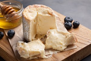 Closeup of Mature cheese on a wooden Board. Soft cheese with honey and blueberries