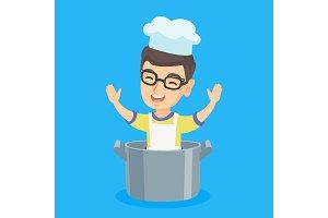 Little caucasian boy sitting in a large saucepan.