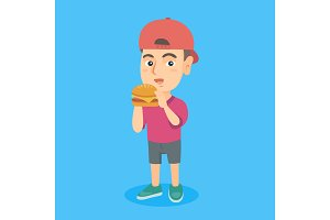 Little caucasian boy eating a hamburger.