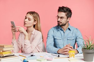 Angry jealous male sits near girlfrind, work together on creating new project work peeps in smart phone tries to see what she does. Blonde female student recieves message, pose against pink background