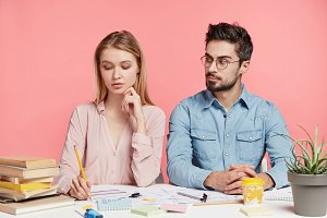 Indoor shot of creative female and male workers sit next to each other, surrounded with papers and books, focused on work, isolated over pink background. People, work, education, cooperation concept