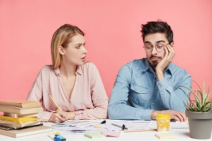 Young female and male students collaborate for making project, hipster guy look in bewilderment at notes, doesn`t know how to do, blonde woman tries make him working. People and work concept.