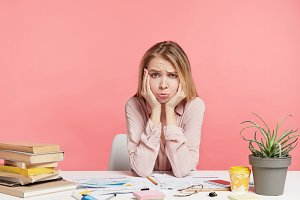 Isolated shot of unhappy displeased pretty female student has problems in studying, feels bored of cramming, surrounded with books, wants to spend time with friends, isolated over pink background