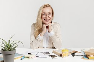 Pleased female enterpreneur sits at workplace, waits for job applicants, going to conduct interview and find suitable candidate on secretary position, has charming smile isolated over white background