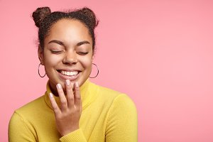 Horizontal portrait of cheerful African female being pleased with something, closes eyes, demonstrates charming smile with perfect white teeth, glad to recieve good news, isolated over pink wall