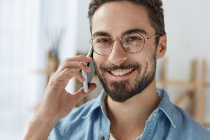 Headshot of attractive bearded young male wears spectacles and denim shirt, has phone converstion with someone via smart phone, smiles happily, demonstrates perfect white teeth, enjoys communication.