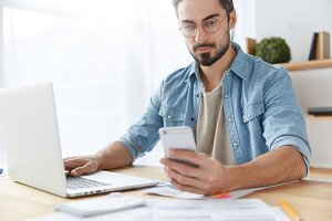 Cropped shot of serious male with beard and mustache does online shopping on smart phone, makes successful purchase, keyboards on laptop computer, sits over office interior. Business concept