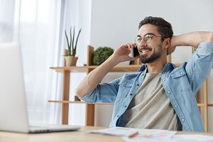 Positive male office worker has break after tired work and long hours of preparation, smiles happily, enjoys loneliness, uses modern gadgets for communication. People and technology concept.