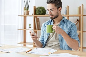 Indoor shot of handsome bearded man dressed casually, holds smart phone and types messages to friends, drinks coffee or tea from mug, has break after working on documents. People and lifestyle