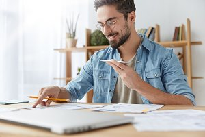 Portrait of cheerful bearded man has voice call, speaks with friend and checks documents, has happy expression. Hardworking male checks finances, does accounting, sits at desk with papers. Job concept
