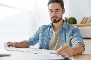 Serious bearded male office worker wears casual clothes, writes in documents, checks information and learns, prepares for business report underlines important things. People and business concept