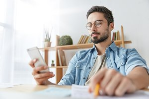 Indoor shot of handsome confident bearded man uses mobile phone for messaging online, holds pencil, has attentive look at screen of gadget. Young clever businessman checks current exchange rate