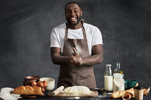 Cheerful African American male cook presents culinary talents, participates in television cooking show, wears apron, stands at kitchen table, makes dough for preparing buns isolated on chalk wall