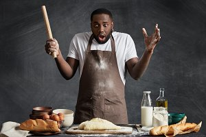 Indoor shot of surprised black man looks with shock at dough he made, holds rolling pin, doesn`t know what to do next, has puzzled expression, poses near kitchen table with different ingredients