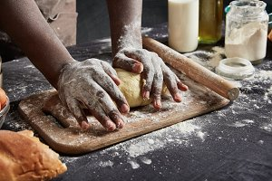 Indoor shot of black man with dirty hands kneads pasrty or dough carefully, uses rolling pin, prepares delicious pizza for guests or relatives, wants to be praised for his culinary abilities. Cooking