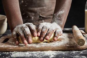 Cropped image of skilled hardworking African American male cook prepares handmade dough, kneads with hands, uses rolling pin. Unrecognizable dark skinned man bakes delicious cakes at kitchen table.