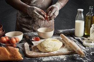 Cropped shot of talented male cook breaks egg in bowl, has dirty hands and apron after making dough and using flour, prepares stuffing for apple pie, uses different ingredients. Baking concept