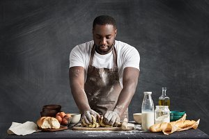 Black male cook wears apron, stands near table with products, shoots video lesson how to make dough for cake or bread, gives advice, kneads pastry gently, shows culinary talents. Housework concept