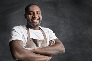 Portrait of cheerful dark skinned black male chef has pleasant smile, keeps hands crossed, being glad to be praised by clients and recieve culinary reward, wears dirty apron, isolated over black wall