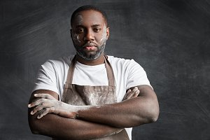 Serious male chef wears apron and casual t shirt, keeps hands crossed, gives commands to unexperinced trainees, has confident expression, poses against black chalk background. Occupation concept