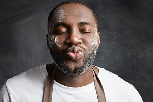 Close up portrait of dark skinned male being satisfied after baking something delicious, roundes lips and closes eyes in enjoyment, has dirty face with flour poses against black chalk background.