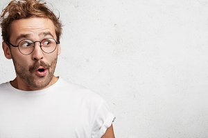 Horizontal shot of amazed bearded male has European appearance wears spectacles, looks in satisfaction aside, sees something wonderful and amazing, poses against white background with copy space