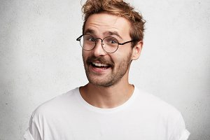 Portrait of cheerful smiling pleasant looking male guy wears round spectacles and casual t shirt, listens with great interest and pleasure interlocutor who tells interesting, intriguing, funny story
