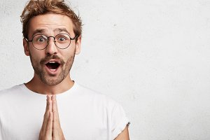 Indoor shot of amazed shocked bearded young man in eyewear keeps palms together, looks with surprisment and great pleasure, poses against white background with copy space. Oh my God, what I see!
