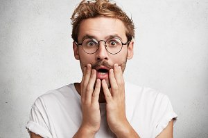 Shocked stupefied male model has trendy hairstyle, mustache and stubble, being in stupor as hears unexpected news from interlocutor, isolated over concrete white wall. Omg and amazement concept